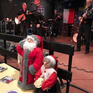 Två tygtomtar på ett litet bord, på scenen ett band, 3 män spelar gitrr och en man sjunger.