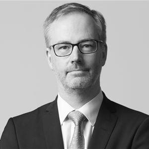 © Per Eriksson, En man med glasögon, svart kostym, vit skjorta och slips med armarna i kors.