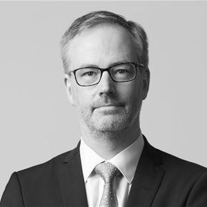 © Per Eriksson, En svartvit bild på en medelålders man i glasögon, mörk kostym, vis skjorta och slips.
