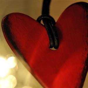 © Magnus Aronson/IKON, Ett rött hjärta i ett läderband, ljus i bakgrunden.