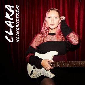 En kvinna med svarta kläder, håller i en vit gitarr, lägger håret bakom örat med ena handen, Klara Klingenström med vit till vänster på bilden.a bokstäver