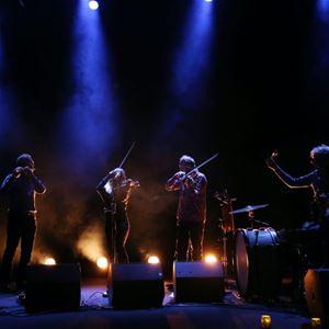Fyra personer som står på en scen, några spelar fiol, det är mörkt i lokalen, strålkastare lyser på musikerna.