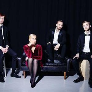Elvira Glänte,  © Elvira Glänte, En tjej med vinröd klänning sitter på en soffa bredvid sig sitter en kille och på varsin sida av soffan sitter två killar.