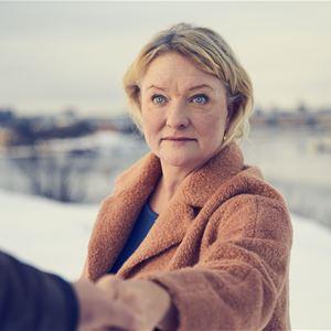 © Klara G, Anna Takanen tar någons hand med ett vinterlandskap i bakgrunden.