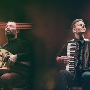 Två män med var sitt instrument, den ena med ett dragspel, den andra med vevlira, strålkastare som lyser.