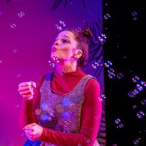 Jonas Jörneberg, En skådespelare blåser såpbubblor mot en lila bakgrund.