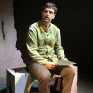 En man i beiga byxor och en ljusgrön tröja, sitter på en bred pall och håller ett papper i handen.