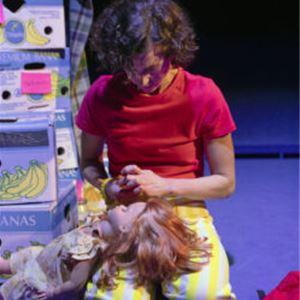En kvinna som sitter på knä, hon har en röd tröja och gulrandiga byxor, i famnen har hon en docka, brevid henne står en trave med banan kartonger.
