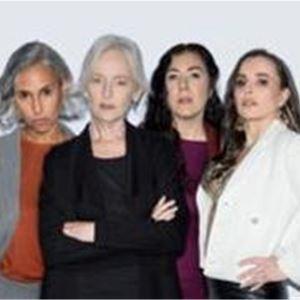 Fyra kvinnor som står brevid varandra, en kvinna i grått axellångt hår med rostfärgad top och grå kostym, en vithårig kvinna i svarta kläder, en kvinna med långt mörkt hår och mörka kläder, en kvinna i långt brunt hår med vit kavaj.