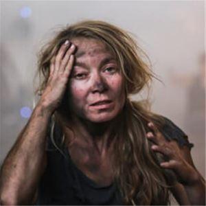 En kvinna med långt hår och smutsigt ansikte, håller ena handen för pannan.