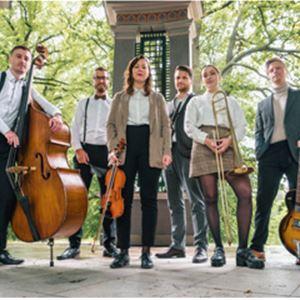 Fyra män och två kvinnor, två av männen har svarta byxor och vita skjortor, en av dem håller i en ståbas, två män i grå kostymer en av dem håller i en gitarr, en av kvinnorna håller i en fiol den andra håller i en trumbon,  pelare och träd i bakgrunden.