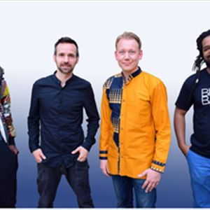 Fyra män som står uppradade, en av dem har en mönstrad jacka, en har mörk skjorta, en har en gul jacka och en svart t-shirt med vitt tryck,  de har antingen händerna i byxfickorna eller längs sidan..