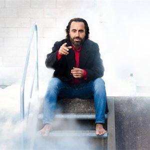 © Sören Vilks, En man i mörkt hår, röd röja, mörk jacka och jeans sitter barfota i en liten ståltrappa, rök runtomkring honom.