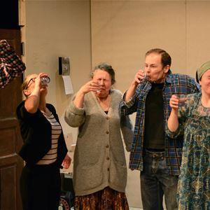 © Jennie Lundgren, Fem personer, en man dricker direkt ur en flaska, tre kvinnor och en man dricker ur glas och grinar illa.