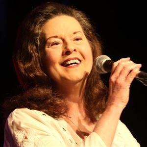 © artist, Linda Gail Lewis har en mikrofon i handen och hon har en vit blus på sig.