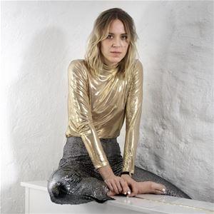 En kvinna med axellångt hår, glittriga silver byxor, en guldfärgad tröja, sitter på en vit möbel, ena benet korslagt över möbeln, en fot utan strumpor eller skor.