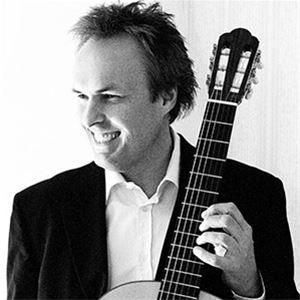 En man i och mörk kavaj, mannen ler och håller en gitarr i handen.vit skjorta