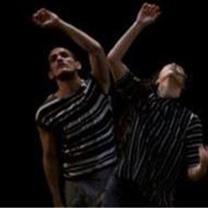 Två män i randiga tröjor, tittar uppåt och sträcker upp en arm i luften.