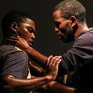 Två män som står mitt emot varandra, en håller i den andras underarmar och den andra håller runt den andres nacke.