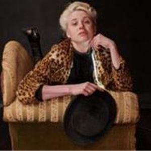 En kvinna med ljust uppsatt hår, kvinnan ligger på en divan, hon har en svart tröja och en leopardmönstrad jacka, hon håller en hatt i handen.