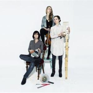 Tre kvinnor, en kvinna i vit skjorta står, en kvinna i mönstrad grå blus sitter på en stol, den tredje kvinnan sitter på en trappstege och håller i en fiol.