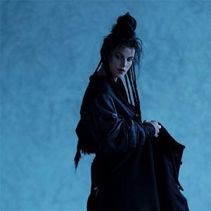 En kvinna i svarta kläder, mörkt uppsatt hår, långa hårslingor som hänger, blå bakgrund.