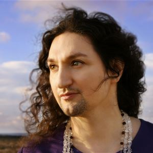 Thomas Di Leva med svart tröja och halsband blickar ut mot en blå himmel.