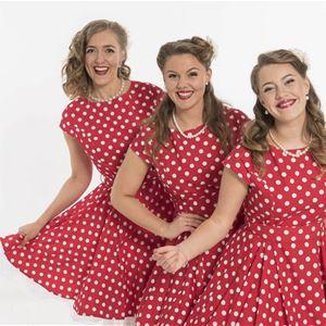Tre kvinnor i röda klänningar med vita prickar, de står på led, alla ler.