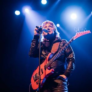 Janne Schaffer på scenen med mikrofon och gitarr.