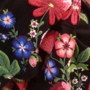 Ett broderi med svart botten och ett mönster med blommor i olika färger.