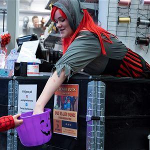 Utklädd kvinna i butik bjuder på godis