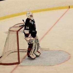 En hockeymålvakt står på isen vid målet.