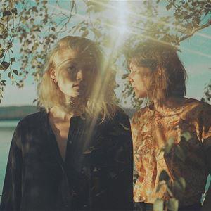 Två kvinnor en av dem i svart skjorta och ljust hår, den andra i en ljus topp och mörkt hår hon står i profil, björk grenar, solen skiner på dem, en sjö i bakgrunden.