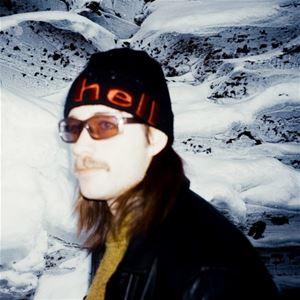 En man i svart mössa, solglasögon, långt hår, gul tröja och svart jacka, i bakgrunden snöklädda berg.