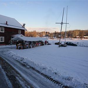 Smal bilväg in till ett stort rött hus med snö som täcker gården.