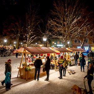 © Jonas Lindgren, Snö på backen, julgran, ljusslingor i träden, marknadsstånd med röd och vitrandiga tak, människor som flanerar runt kring stånden.