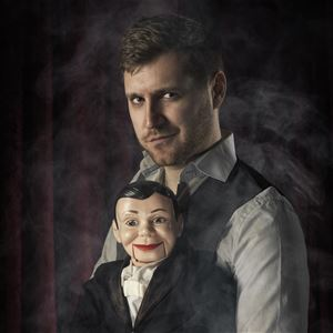 © Stefan Krämer, Marcus Lindh i grå skjorta och svart väst håller buktalardockan Charlie iklädd svart kostym.