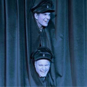 Två män sticker fram huvudena genom ett draperi, båda har polismössor på huvudet.