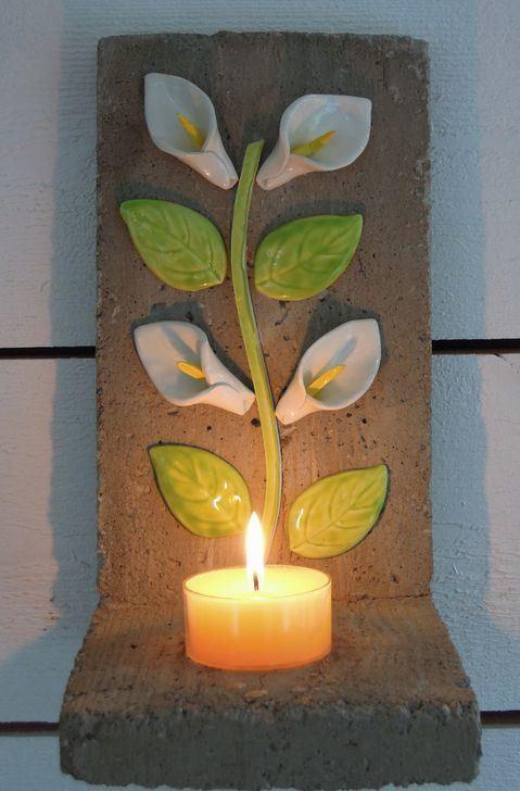 väggljusstake i betong dekorerad med handgjorda liljor och blad.
