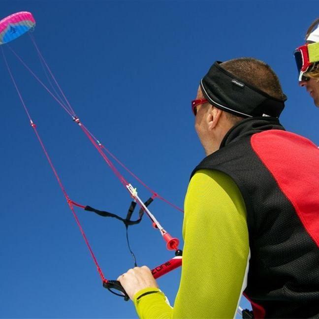 Foto: Johan Marklund,  © Foto:Johan Marklund, En person med tröja och väst, pannabnd och solglasöghon som håller i en kite.