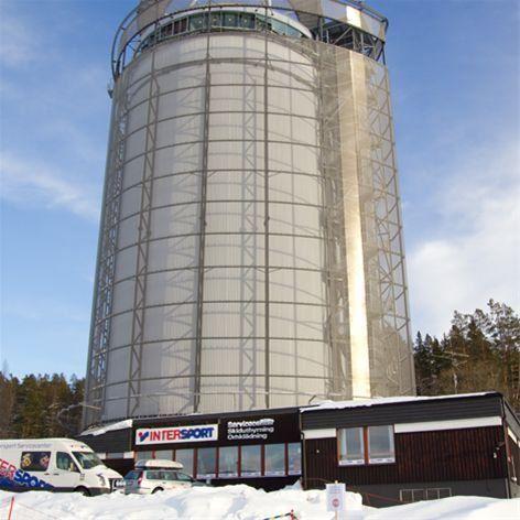 Foto: Intersport,  © Copy: Intersport, Fjärrvärmetornet Arctura med ett lågt hus framför samt en skåpbil.