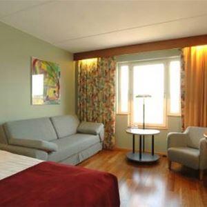 Hotellrum, dubbelsäng, skrivbord, soffa och fåtölj.