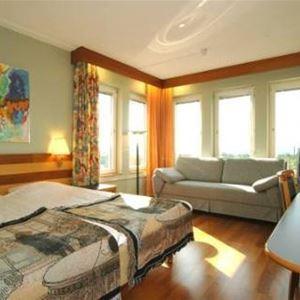 Hotellrum, dubbelsäng, skrivbord och soffa.