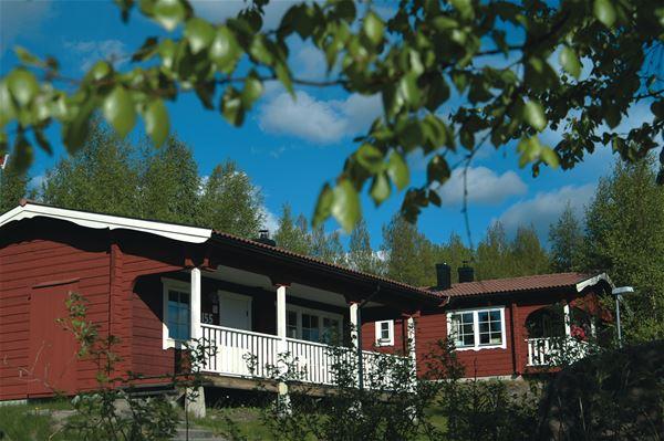 Röd stuga med stor veranda.