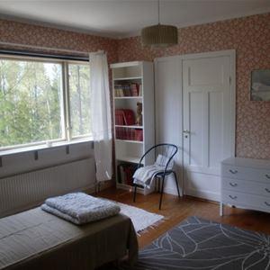 Sovrum med en enkelsäng och ett stort fönster.