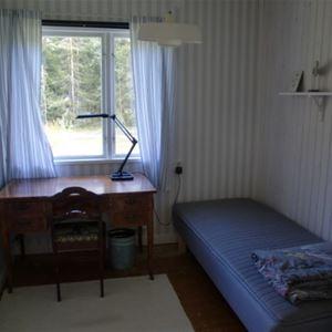 Sovrum med enkelsäng och ett skrivbord framför fönstret.