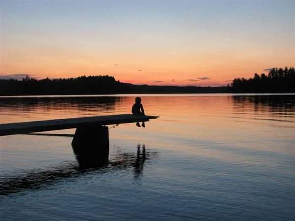 Solnedgång vid sjö med siluett av barn på brygga.