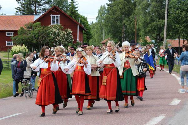 fiolspelande män och kvinnor i folkdräkt tågar i samlad trupp till Midsommarfirande.