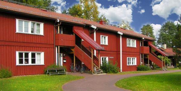 Röd tvåvåningsbyggnad med flera entréer och takad trapp till övervåningen.