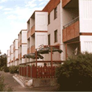 Exteriörbild på vandrarhemmet som ligger i en lägenhetslänga med två våningar.